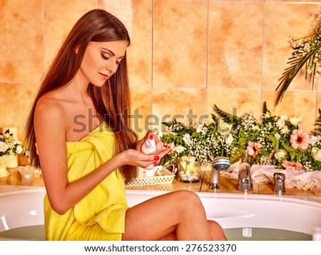 Woman applying moisturizer at bathroom. Yellow towel. - stock photo