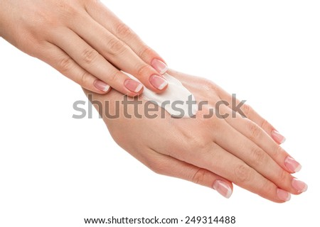 Woman applying moisturizer cream on hands with french manicure