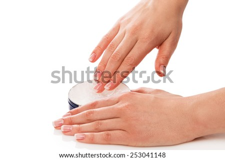 Woman applying moisturizer cream on hands with french manicure - stock photo