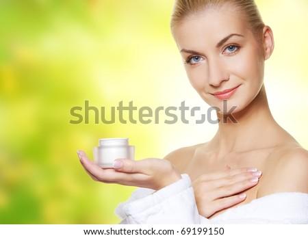 Woman applying moisturizer cream on her body - stock photo