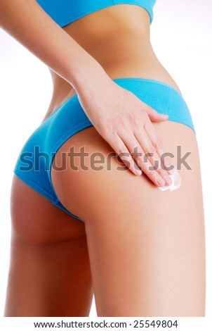 Woman applying moisturizer cream on legs. Perfect female figure - stock photo