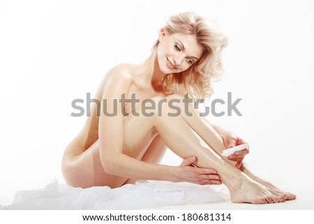 Woman applying moisturizer cream on the legs over white background - stock photo