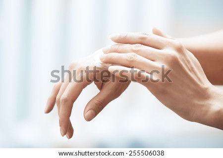 Woman applying moisturizing cream on hands - stock photo