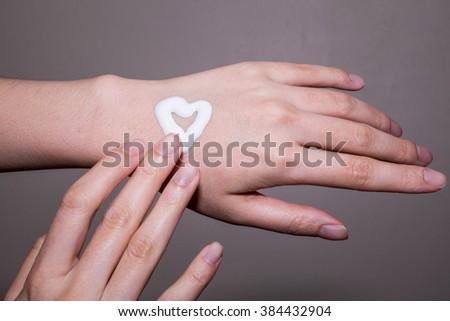Woman applying moisturizing cream on hands - stock photo