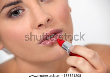 Woman applying red lipstick - stock photo