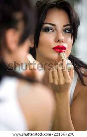 woman applying red lipstick and reflected in the mirror - stock photo