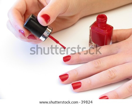 woman applying red nail polish on white background - stock photo