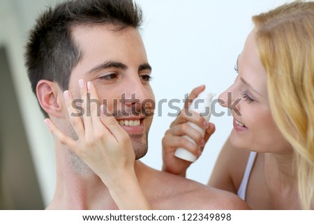 Woman applying sunscreen on her boyfriend's cheeks - stock photo