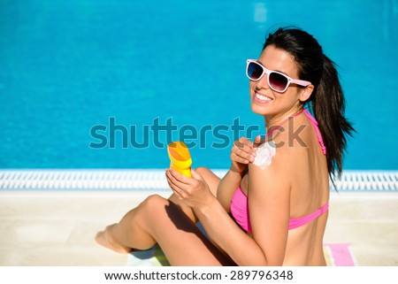 Woman applying sunscreen or suntan lotion in her shoulder for solar skin protection at swimming pool. Brunette girl enjoying summer vacation. - stock photo