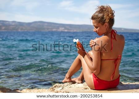 Woman applying sunscreen solar cream.  - stock photo