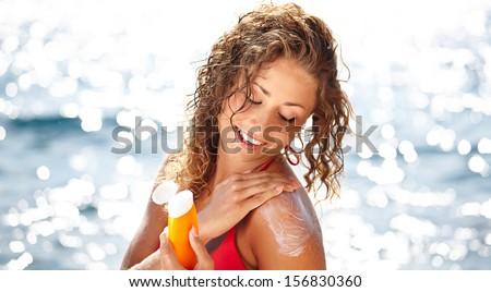 woman applying suntan lotion at the beach smiling  - stock photo