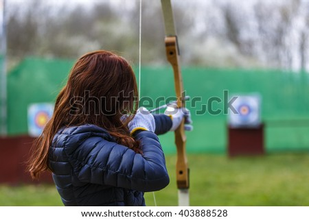 woman archer shooting with his bow at an outdoor archery range