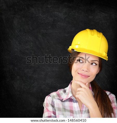 Woman architect, engineer, surveyor or construction worker wearing protection hardhat thinking looking thoughtfully to the side on chalkboard blackboard texture for copy space. - stock photo
