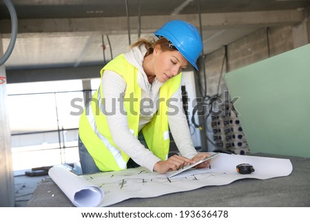 Woman architect on building site using tablet - stock photo