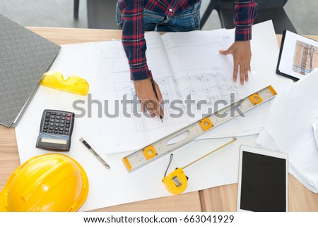 Woman architect working blueprint on table stock photo royalty free woman architect working blueprint on table wood inspective in workplace architectural project malvernweather Gallery