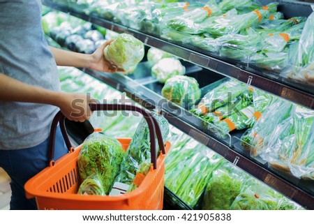 Woman are choosing vegetable in supermarket - stock photo