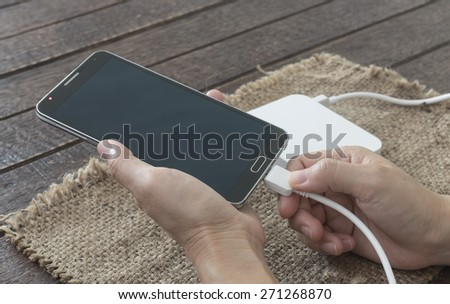 woman are connected charging cable to the smartphone by external battery. - stock photo