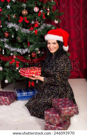 Woman arrange Xmas gifts near  tree in her home - stock photo