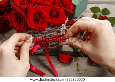 Woman arranging bouquet of red roses