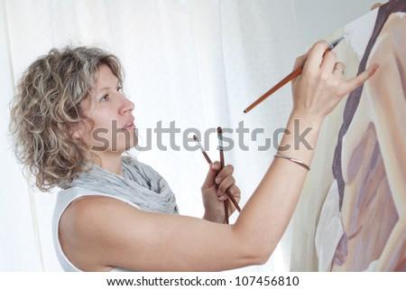 Woman artist draws a portrait of a woman. - stock photo