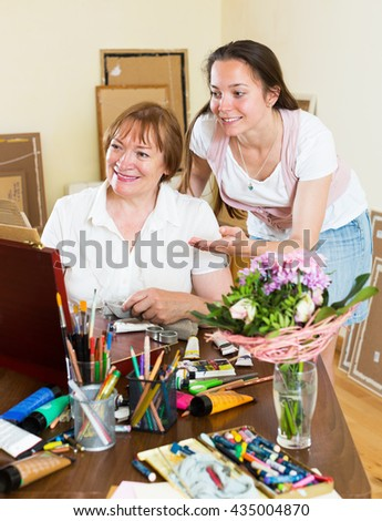 Woman artist painting a picture for her admirer at studio - stock photo