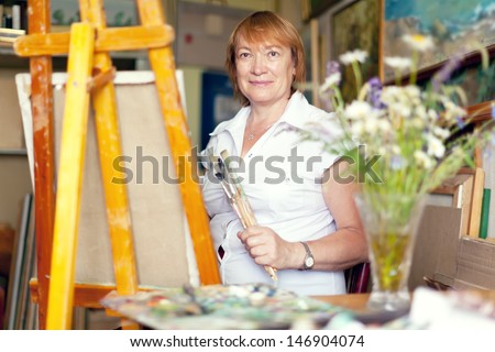 woman artist paints the flowers on canvas in studio - stock photo