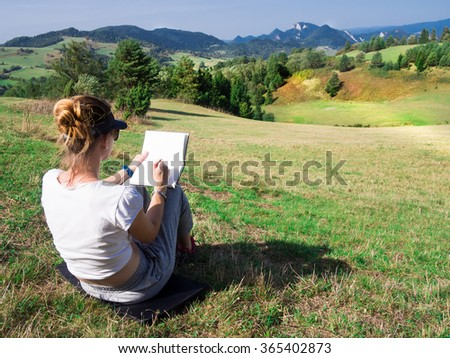Woman artist working outdoors on hillside