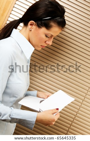 woman as office worker is reading notice of layoff