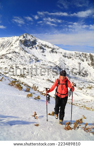 Woman ascending a snowy trail on the mountain in fine weather - stock photo