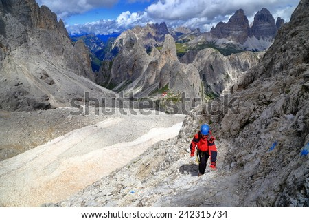 "Woman ascending a steep trail to via ferrata ""Merlone"" in Cadini di Misurina, Dolomite Alps, Italy - stock photo"