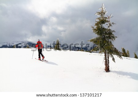 Woman ascending during ski touring in the mountains, Romania