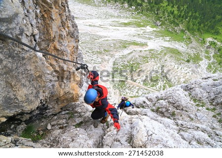 "Woman ascending steep walls of Sella massif while climbing via ferrata ""Meisules"", Dolomite Alps, Italy"