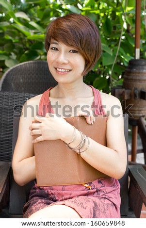Woman asia sitting and reading notebook in outdoor.