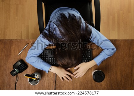 woman asleep at her desk taken from a birds eye view