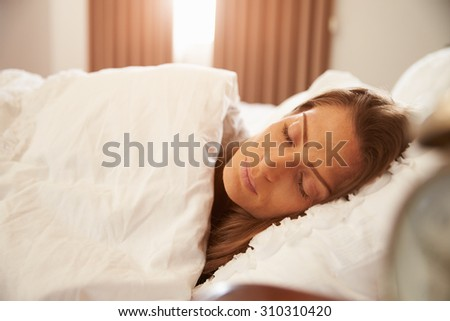 Woman Asleep In Bed As Sunlight Comes Through Curtains - stock photo