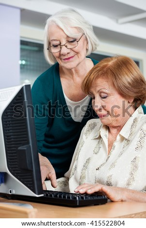 Woman Assisting Female Friend In Using Computer At Classroom - stock photo