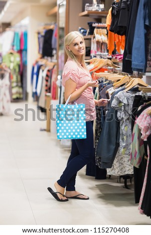 Woman at a shopping mall holding a bag smiling