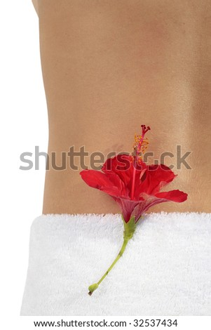 Woman at a spa with a red hibiscus flower on her back