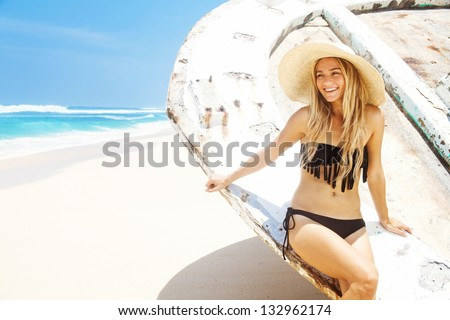 woman at abandoned old boat on the beach, bali, indonesia - stock photo
