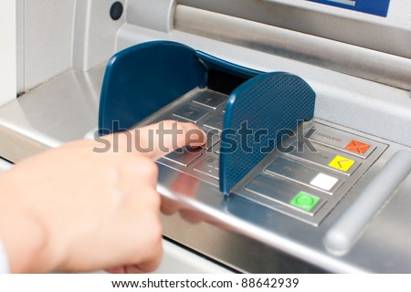 Woman at ATM or cash dispenser and is entering her PIN; only hand to be seen