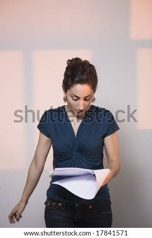 Woman at audition, reading script - stock photo