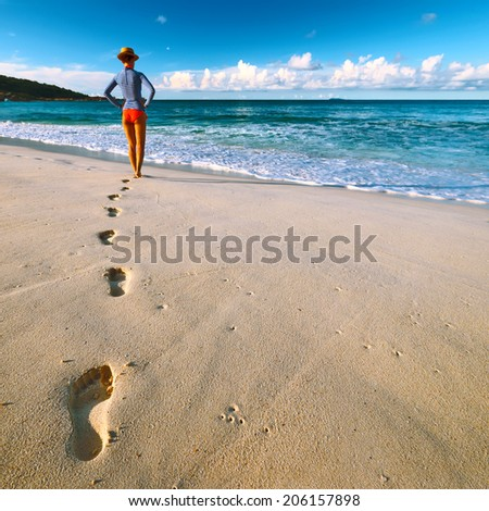 Woman at beautiful beach at Seychelles walking on sand. Focus on footprints. - stock photo