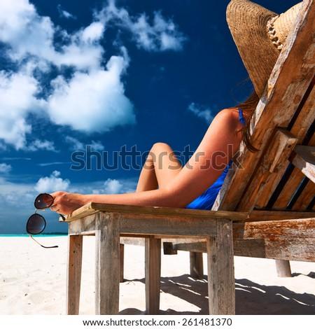 Woman at beautiful beach holding sunglasses - stock photo