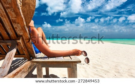 Woman at beautiful beach holding sunglasses