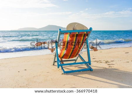 Woman at beautiful beach relaxing on a sunbed - stock photo