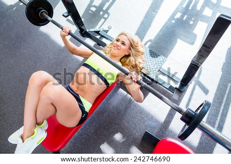 Woman at bench press in gym exercising for better fitness - stock photo
