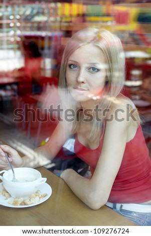 Woman at cafe looking in the window . Eating soup. - stock photo