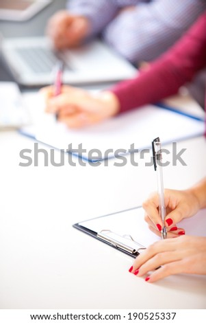 Woman at class desk signing a contract with shallow focus on pen