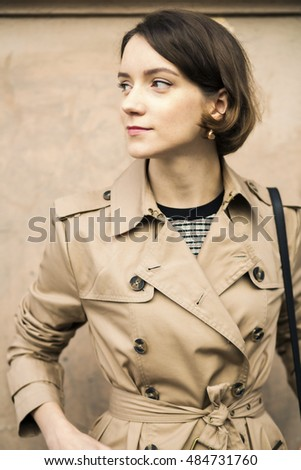 Woman at coat with handbag looking aside