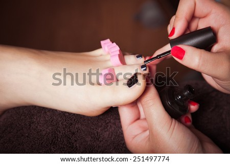 woman at cosmetics salon applying black  nail polish on toenails - stock photo